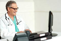 Ervaren arts die aan computer werkt Stock Afbeelding