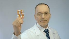 Ervaren arts die pak capsules voor camera, de farmaceutische industrie tonen stock videobeelden