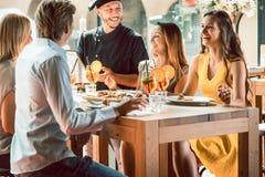 Ervaren die chef-kok door vier mensen bij een in restaurant wordt gelukgewenst royalty-vrije stock fotografie