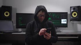 Ervaren hakkerhouweren op de klanten` s bankrekening die een smartphone en een plastic creditcard gebruiken jonge mens binnen stock video