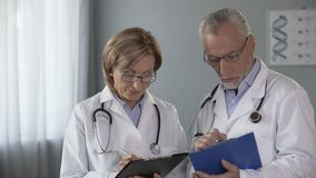 Ervaren mannelijke en vrouwelijke artsen die resultaten vergelijken, die bij de diagnose raadplegen stock footage
