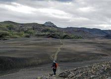 Ervaren mannelijke wandelaar die alleen in de wildernis met zware rugzak in zwarte woestijn, Laugavegur-wandelingssleep, IJsland  stock foto's