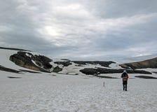 Ervaren mannelijke wandelaar die alleen in de wildernis wandelen die geothermisch die landschap bewonderen met sneeuw, zware rugz royalty-vrije stock fotografie