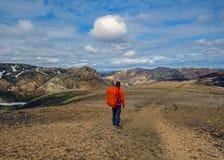Ervaren mannelijke wandelaar die alleen in de wildernis wandelen die vulkanisch landschap met zware rugzak bewonderen Het avontuu royalty-vrije stock fotografie