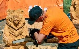 Ervaren timmerman die grote houten maken beeldhouwwerk met een kettingzaag dragen royalty-vrije stock afbeeldingen