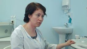 Ervaren vrouwelijke arts die aan patiënt in het ziekenhuis spreken stock video