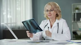 Ervaren vrouwelijke radioloog die Röntgenfoto, gekwalificeerde diagnostiek bestuderen stock videobeelden
