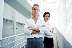 Ervaren vrouwenondernemer met partner het stellen in modern wit bureaubinnenland die zeker kijken, Stock Afbeelding