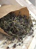 Ervas do tomilho em um saco de papel em um fundo de madeira da escadaria fotografia de stock