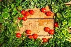 Ervas e tomates vegetais verdes em uma tabela de madeira Foto de Stock Royalty Free