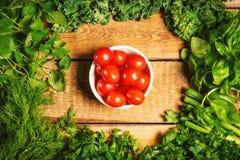 Ervas e tomates vegetais verdes em uma tabela de madeira Imagem de Stock Royalty Free