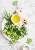 Ervas, especiarias e azeite do jardim em uma tabela clara Da cozinha vida ainda Ingredientes para cozinhar Fotos de Stock Royalty Free