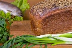 Ervas frescas pão e peixes tradicionais em uma placa de madeira Fotografia de Stock