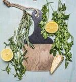 Ervas, limão, raiz de aipo em um lugar da placa de corte para o fim rústico de madeira da opinião superior do fundo do texto acim Fotografia de Stock Royalty Free