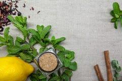 Ervas para o chá e um limão em um fundo de linho imagens de stock royalty free