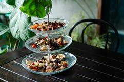 Ervas secadas aromáticas em uma bandeja de vidro ajustada em café com ar condicionado 4 fotos de stock