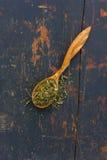 Ervas secadas em uma colher de madeira imagens de stock