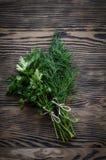 Ervas verdes frescas do aneto e da salsa na tabela de madeira rústica Vista superior com espaço da cópia Fotografia de Stock