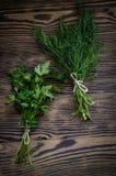 Ervas verdes frescas do aneto e da salsa na tabela de madeira rústica Vista superior com espaço da cópia Fotografia de Stock Royalty Free