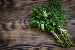 Ervas verdes frescas do aneto e da salsa na tabela de madeira rústica Vista superior com espaço da cópia Imagens de Stock
