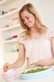 Ervilha de rachadura da mulher nova na cozinha Fotografia de Stock