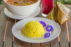 Ervilha do arroz e de borboleta da cúrcuma na placa branca Alimento tailandês da tradição em uma tabela de madeira Estilo tailand fotografia de stock royalty free