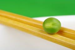 Ervilha em um par de Chopsticks Fotos de Stock