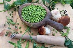Ervilhas verdes e cogumelos em um woode Fotos de Stock Royalty Free