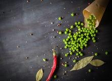 Ervilhas verdes em um papel e em pimentas de pimentão em um fundo de madeira escuro Imagens de Stock Royalty Free