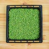 Ervilhas verdes em uma bacia em uma tabela de madeira branca Fotografia de Stock Royalty Free