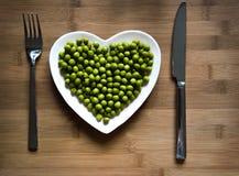 Ervilhas verdes em uma placa coração-dada forma Fotografia de Stock Royalty Free