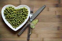 Ervilhas verdes em uma placa dada fôrma coração Fotografia de Stock
