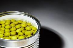 Ervilhas verdes enlatadas em uma lata de lata fotografia de stock royalty free