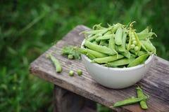 Ervilhas verdes frescas em uma bacia branca sobre foto de stock