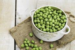 Ervilhas verdes frescas em uma bacia, na tabela Imagens de Stock