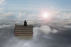 Erwägen des Geschäftsmannes, der auf Stapel Büchern mit Sonnenlichtcl sitzt Stockbild