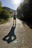 Erwärmungsarme des Läufers mit großem Schatten Stockfotografie