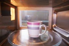 Erwärmungstasse kaffee innerhalb des Mikrowellenherds Lizenzfreie Stockbilder
