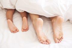 Erwachsen- und Babyfüße unter der Decke Stockbild