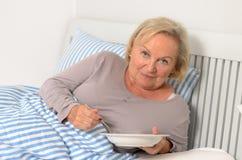 Erwachsene blonde Frau auf ihrem Bett, das ihr Lebensmittel hält Lizenzfreies Stockfoto