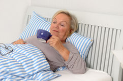 Erwachsene blonde Frau auf ihrem Bett, das ihre Schale hält Stockfoto