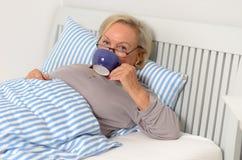 Erwachsene blonde Frau auf ihrem Bett, das ihre Schale hält Stockfotografie