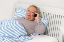 Erwachsene blonde Frau auf ihrem Bett, das ihren Handy hält Stockbild