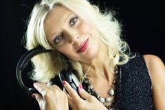 Erwachsene blonde Frau, die mit Kopfhörern in ihren Händen lächelt Stockfotos