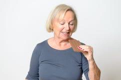 Erwachsene blonde Frau, die oben Schokoriegel im Abschluss isst Stockfotografie