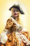 Erwachsene blonde Frau im venetianischen Kostüm Steigungswandhintergrund Stockfotos