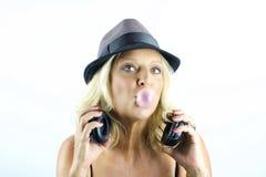 Erwachsene blonde Frau mit dem Hut und Kopfhörern, die mit Blase spielen Stockfotografie