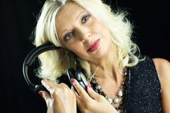 Erwachsene blonde Frau mit Kopfhörern nähern sich ihrem Gesicht Lizenzfreies Stockbild
