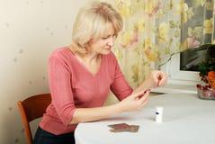 Erwachsene blonde Frau mit Pillen Stockbild