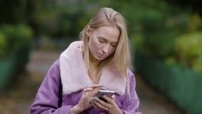 Erwachsene blonde Geschäftsfrau steht allein im Park und in Schreibenmitteilung auf ihrem Smartphone in der Tageszeit stock video
